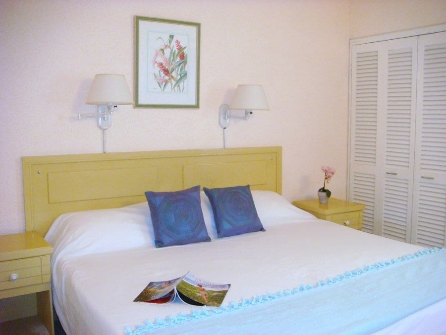 Stay at Plum Tree Club Apartments in a bedroom with king sized beds.